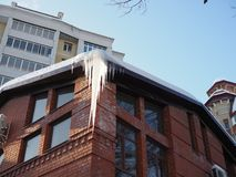 Icicles hang from roof of building. Danger for passers, threat of death and injury from icicles royalty free stock image