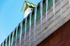 Icicles hang from the roof of the house. Spring. At the end of March, there are icicles Royalty Free Stock Photos