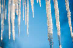 Icicles hanging against a blue sky Stock Photo