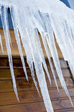 Icicles hanging from a building. Large frozen icicles hanging from the roof of a house Stock Images
