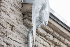 Icicles hanging from building drainpipe Stock Photography