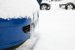 Icicles hanging on the car bumper with snow Stock Images