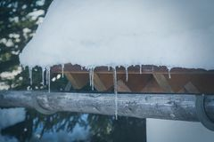 Icicles hanging down off a snow covered roof. Of a wooden chalet or hut on a cold winter day in a close up view Royalty Free Stock Photo