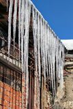 Icicles hanging down from a roof in the early spring. Spring, sunny day, but at night frost. Spring drops. Icicles are very danger. Ous for people`s life stock images