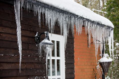 Icicles hanging from a drainpipe ouside a house Royalty Free Stock Image