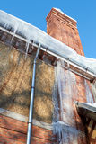 Icicles Hanging From A Drainpipe On A rural House Stock Images