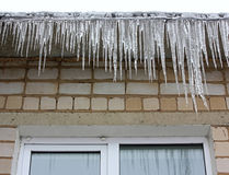 Icicles hanging on the eaves Stock Photos