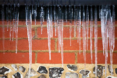 Icicles hanging in front of a stone wall Stock Photo