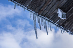 Icicles hanging from house roof against blue sky background Royalty Free Stock Photography
