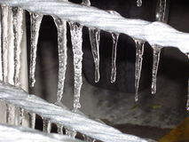 Icicles hanging from a metal wire. A row of frozen icicles, frozen water, hanging from a metal wire during a cold winter Stock Images
