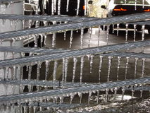 Icicles hanging from a metal wire. Rows of frozen icicles, frozen water, hanging from metal wires in a parking garage during a cold winter. The ice is dripping Stock Photography
