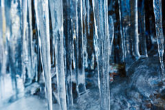 Icicles hanging on mountain rock Stock Images