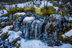 Icicles hanging on mountain rock Royalty Free Stock Photos