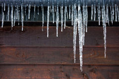Icicles hanging outside a wooden panelled house Stock Images