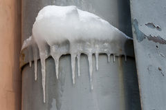 Icicles hanging over a frozen water tube at roof. cold weather. Winter background. soft focus Stock Photography