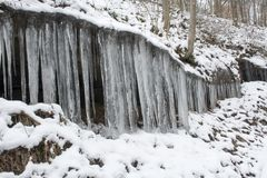 Icicles hanging from rock outcropping royalty free stock photo
