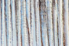 Icicles hanging on the roof Stock Photos