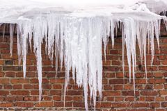 Icicles hanging from the roof of the building - danger to human royalty free stock photography