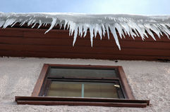 Icicles hanging from roof on house Royalty Free Stock Photography