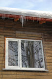Icicles hanging from roof on house Royalty Free Stock Images