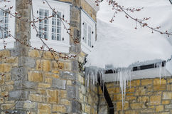 Icicles hanging on the roof of the house Stock Photography