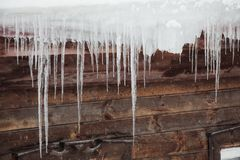 Icicles hanging on the roof royalty free stock photo