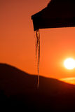 Icicles reflecting the sunset. Icicles hanging from a roof with mountains and a beautiful sunset in the background Royalty Free Stock Images