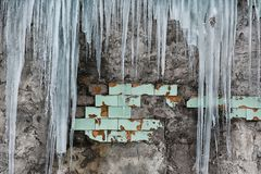 Icicles hanging from the roof of the old brick building with cubes of old tiles, traumatic acrid ice, thaw in the early spring, se Royalty Free Stock Photo