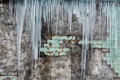 Icicles hanging from the roof of the old brick building with cubes of old tiles, traumatic acrid ice, thaw in the early spring, se Stock Photography