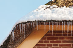 Icicles hanging on the roof of an old Dutch farm Royalty Free Stock Photos