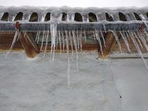 Icicles hanging on roof of old house, close-up. Winter in Ukrainian village stock photo