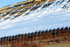 Icicles hanging on a roof. Stock Image