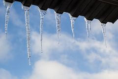 Icicles hanging on roof at winter. Natural ice formation of ice crystals hanging on roof edge at winter Royalty Free Stock Photos