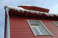 Icicles hanging from roof on wood house Royalty Free Stock Photos