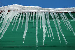 Icicles hanging from roof on wooden house Royalty Free Stock Images