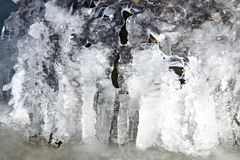 Icicles hanging over bolders in creek Royalty Free Stock Photography