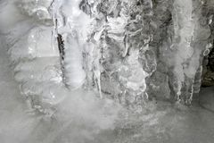 Icicles hanging over bolders in creek stock photos