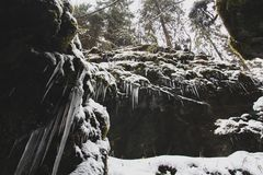 Icicles hanging from snow-covered rocks royalty free stock photography
