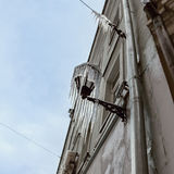 Icicles hanging from a streetlamp. Facade of the old building wi Royalty Free Stock Photo