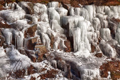 Icicles on a hillside. Dripping frozen water formed into icicles on a rocky hillside in New Hampshire Stock Photography
