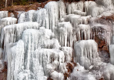 Icicles on a hillside II. Dripping frozen water formed into icicles on a rocky hillside in New Hampshire Stock Photo