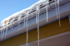 Icicles on house eaves. Ice, snow and icicles on house eaves Royalty Free Stock Image