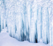 Icicles on the ice wall. Icicles background on the ice wall on Baikal lake at winter Royalty Free Stock Photo