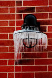 Icicles On Lamp. Icicles hang on black lamp on red brick wall Royalty Free Stock Photos