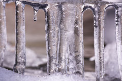 Icicles that melted and fell off the roof into the snow Stock Photography