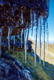 Icicles on a mountain cliff Stock Photo