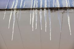 Icicles on the office building. The season of icicles on roofs of houses Stock Photography