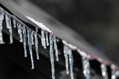 Icicles on an old iron roof Stock Photos