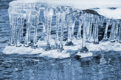 Icicles over water Royalty Free Stock Photos