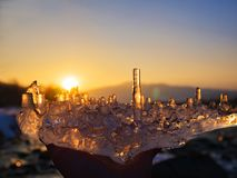 Icicles a piece of ice in hand against the backdrop of a mountain river at sunset royalty free stock photo